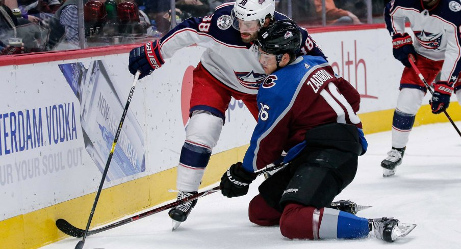 Feb 5, 2019; Denver, CO, USA; Columbus Blue Jackets center Boone Jenner (38) and Colorado Avalanche defenseman Nikita Zadorov (16) battle for the puck in the first period at the Pepsi Center.