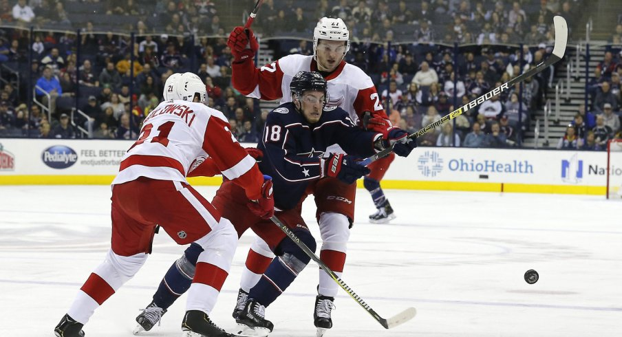 Oct 30, 2018; Columbus, OH, USA; Columbus Blue Jackets left wing Pierre-Luc Dubois (18) chips the puck by Detroit Red Wings defenseman Dennis Cholowski (21) and center Michael Rasmussen (27) during the second period at Nationwide Arena. Mandatory Credit: Russell LaBounty-USA TODAY Sports