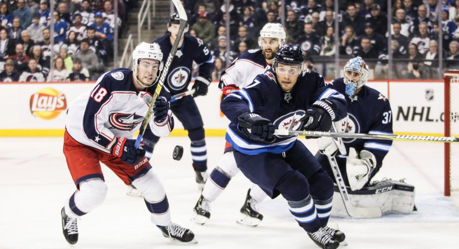 Jan 31, 2019; Winnipeg, Manitoba, CAN; Winnipeg Jets defenseman Ben Chiarot (7) and Columbus Blue Jackets forward Pierre Luc Dubois (18) eye the puck during the second period at Bell MTS Place.