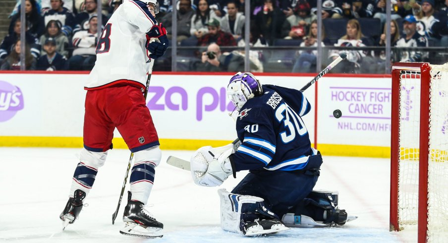 Nov 23, 2019; Winnipeg, Manitoba, CAN; Winnipeg Jets goalie Laurent Brossoit (30) makes a save with Columbus Blue Jackets forward Pierre Luc Dubois (18) looking for a rebound during the first period at Bell MTS Place. Mandatory Credit: Terrence Lee-USA TODAY Sports
