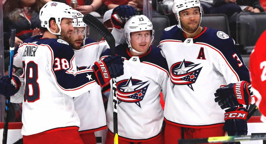 Columbus Blue Jackets right wing Oliver Bjorkstrand (28) receives congratulations from teammates after scoring in the first period against the Detroit Red Wings at Little Caesars Arena.