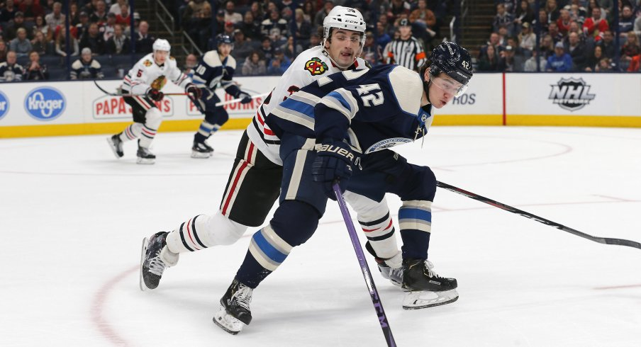 Dec 29, 2019; Columbus, Ohio, USA; Chicago Blackhawks defenseman Dennis Gilbert (39) steals the puck from Columbus Blue Jackets center Alexandre Texier (42) during the first period at Nationwide Arena.