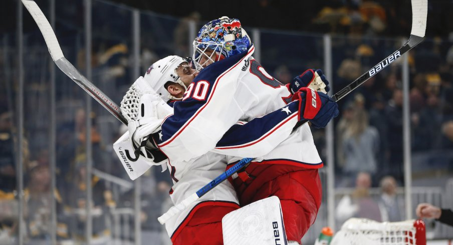 Columbus Blue Jackets goaltender Elvis Merzlikins (90) jumps into the arms of left wing Nick Foligno (71) after defeating the Boston Bruins in overtime at TD Garden.