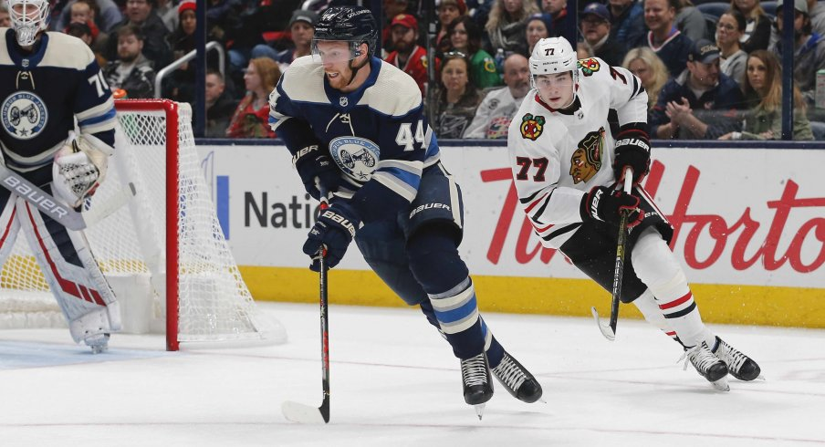 Dec 29, 2019; Columbus, Ohio, USA; Columbus Blue Jackets defenseman Vladislav Gavrikov (44) carries the puck away from Chicago Blackhawks center Kirby Dach (77) during the second period at Nationwide Arena.