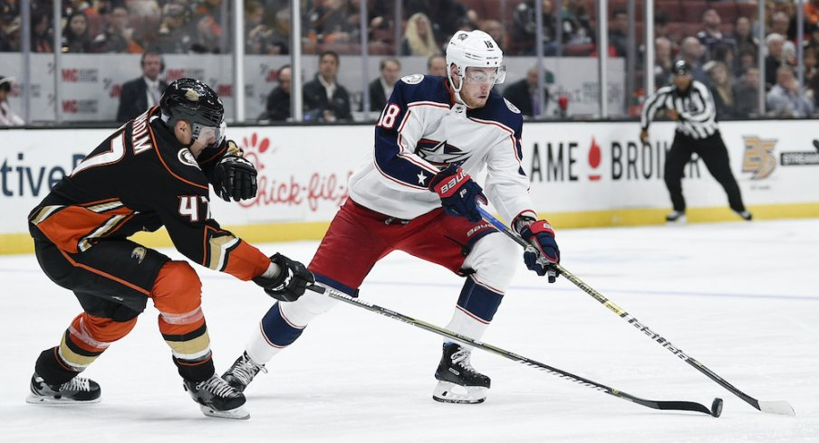 Columbus Blue Jackets center Pierre-Luc Dubois (18) handles the puck while under pressure by Anaheim Ducks defenseman Hampus Lindholm (47) during the second period at Honda Center.