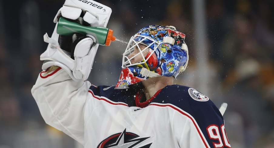 Columbus Blue Jackets goaltender Elvis Merzlikins (90) sprays water on his face during the third period against the Boston Bruins at TD Garden.