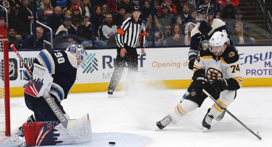 Columbus Blue Jackets goalie Elvis Merzlikins (90) makes a save from the shot of Boston Bruins left wing Jake DeBrusk (74) during the first period at Nationwide Arena.