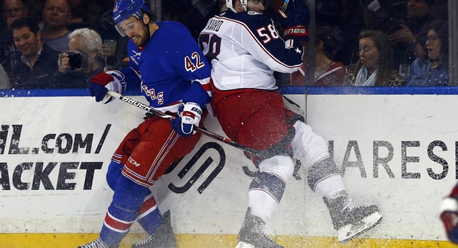 New York Rangers defenseman Brendan Smith (42) and Columbus Blue Jackets defenseman David Savard (58) battle for the puck during the second period at Madison Square Garden.