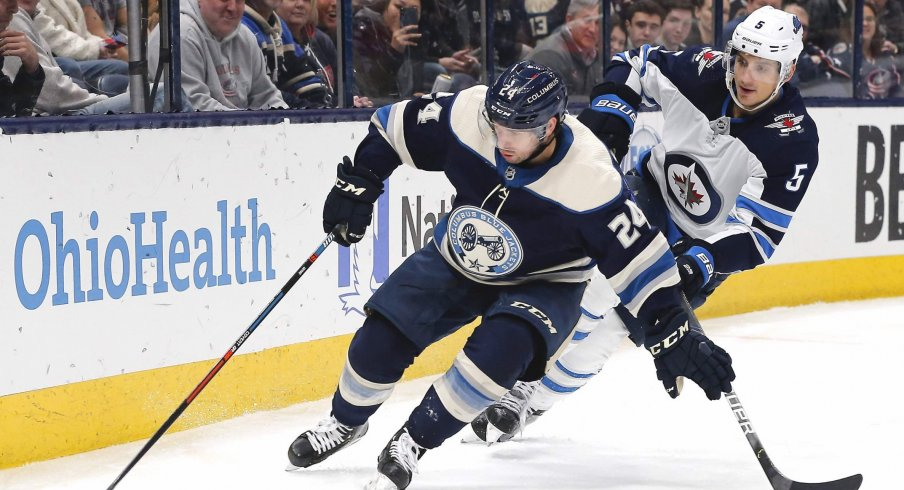 Jan 22, 2020; Columbus, Ohio, USA; Columbus Blue Jackets center Nathan Gerbe (24) carries the puck away from Winnipeg Jets defenseman Luca Sbisa (5) during the second period at Nationwide Arena.