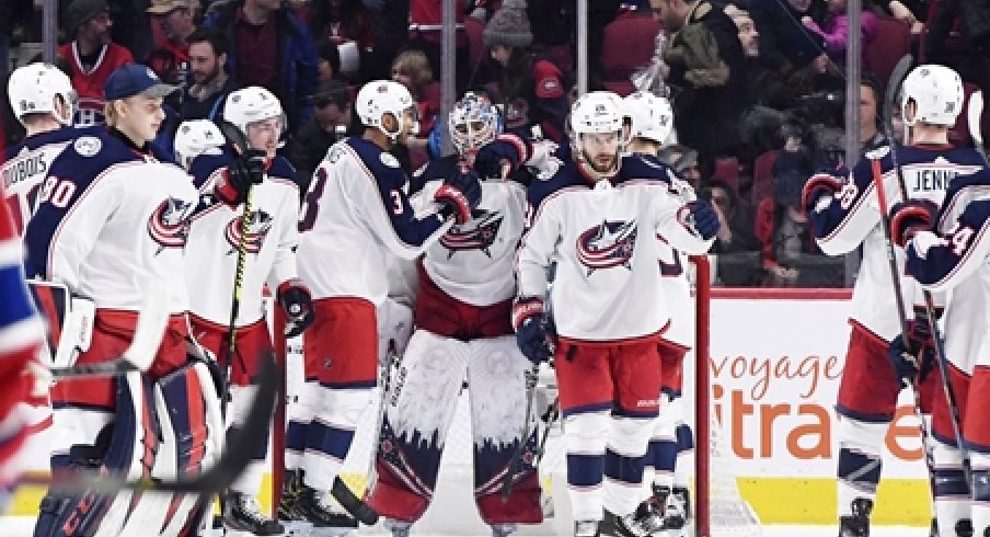 The Columbus Blue Jackets surround goaltender Elvis Merzlikins after a win over the Montreal Canadiens at the Bell Centre.