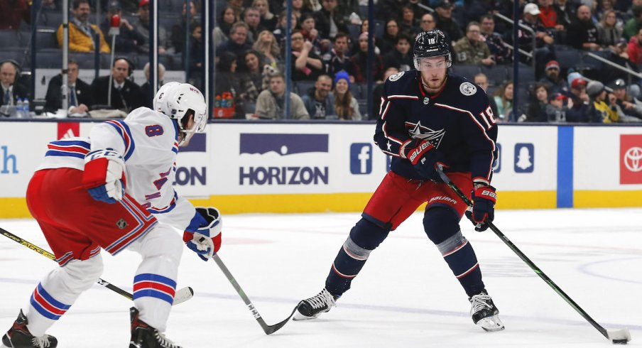 Columbus Blue Jackets center Pierre-Luc Dubois (18) passes the puck as New York Rangers defenseman Jacob Trouba (8) defends during the first period at Nationwide Arena.