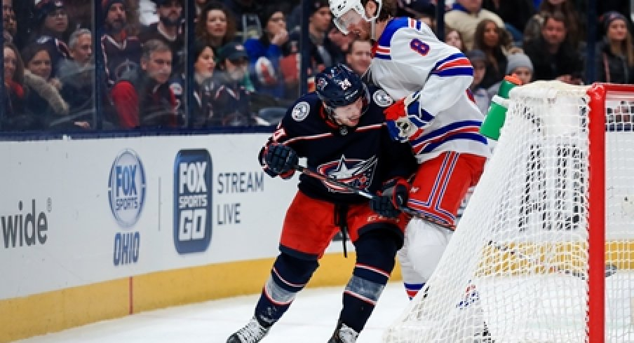 Columbus Blue Jackets forward Nathan Gerbe fights for the puck alongside New York Rangers defenseman Jacob Trouba during a game at Nationwide Arena.