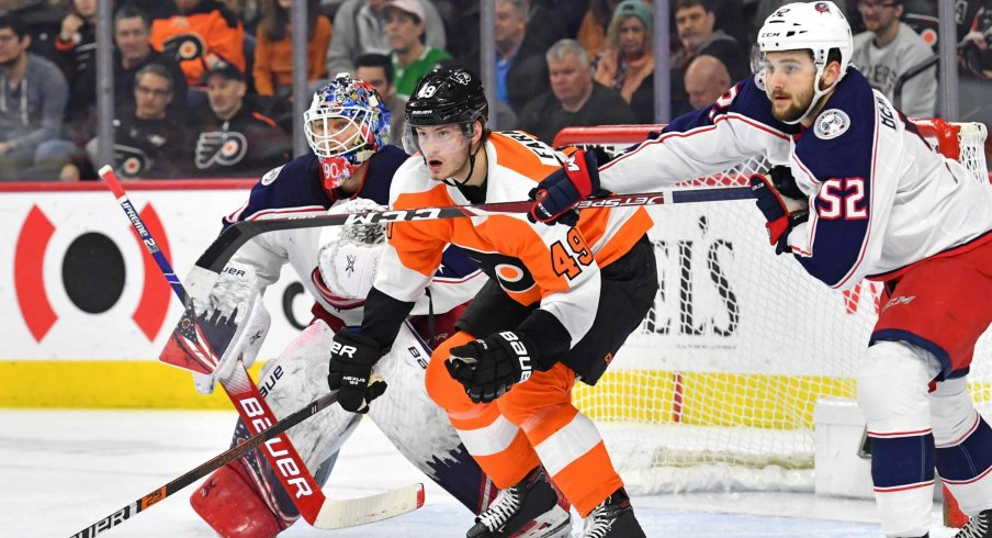 Feb 18, 2020; Philadelphia, Pennsylvania, USA; Philadelphia Flyers left wing Joel Farabee (49) fights for position with Columbus Blue Jackets center Emil Bemstrom (52) in front of goaltender Elvis Merzlikins (90) during the second period during the first period at Wells Fargo Center.