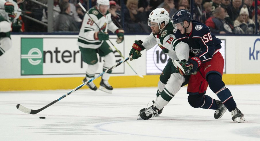 Feb 28, 2020; Columbus, Ohio, USA; Minnesota Wild left wing Jordan Greenway (18) and Columbus Blue Jackets left wing Eric Robinson (50) battle for the puck during the game at Nationwide Arena.