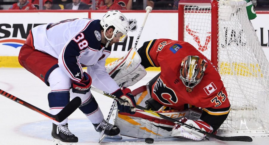 Calgary Flames goalie David Rittich (33) makes a save against Columbus Blue Jackets center Boone Jenner (38) during the second period at Scotiabank Saddledome.