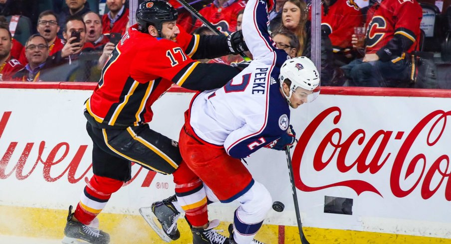 Mar 4, 2020; Calgary, Alberta, CAN; Columbus Blue Jackets defenseman Andrew Peeke (2) and Calgary Flames left wing Milan Lucic (17) battle for the puck during the first period at Scotiabank Saddledome.