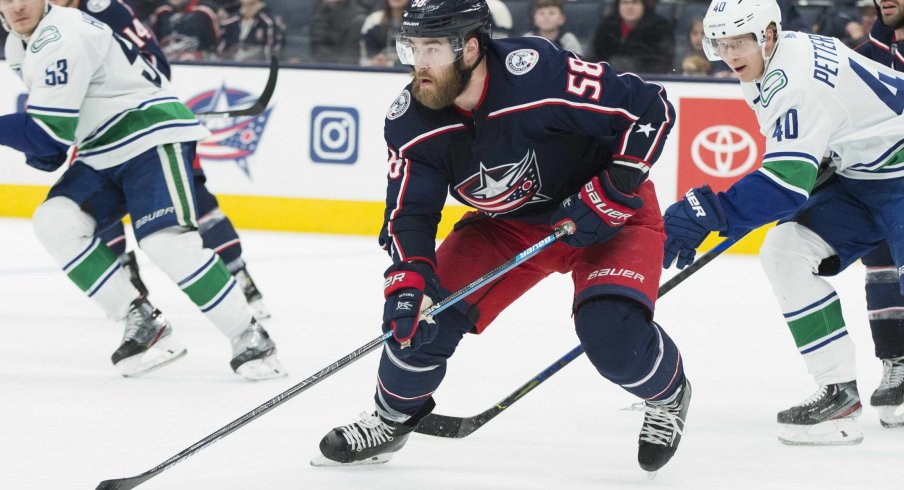 Columbus Blue Jackets defenseman David Savard (58) advances the puck defended by Vancouver Canucks center Elias Pettersson (40) in the third period at Nationwide Arena.