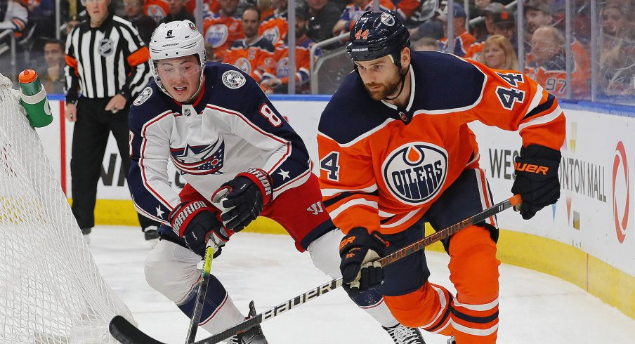 Mar 7, 2020; Edmonton, Alberta, CAN; Columbus Blue Jackets defensemen Zack Werenski (8) and Edmonton Oilers forward Zack Kassian (44) battle for a loose puck during the first period at Rogers Place.