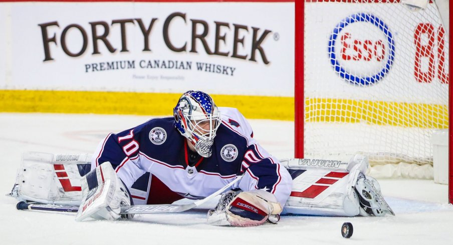 Columbus Blue Jackets goaltender Joonas Korpisalo (70) makes a save against the Calgary Flames during the third period at Scotiabank Saddledome.