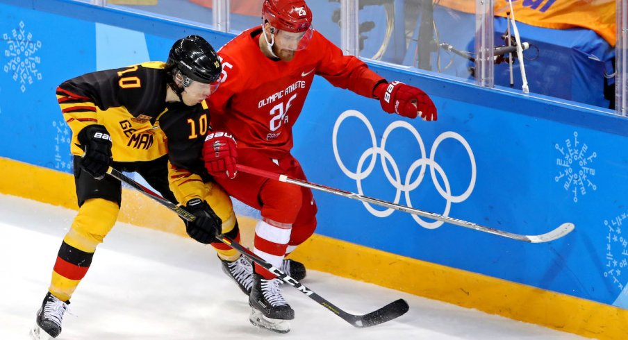 Germany defenseman Christian Ehrhoff (10) and Olympic Athlete from Russia forward Mikhail Grigorenko (25) go for the puck in the men's ice hockey gold medal match during the Pyeongchang 2018 Olympic Winter Games at Gangneung Hockey Centre.