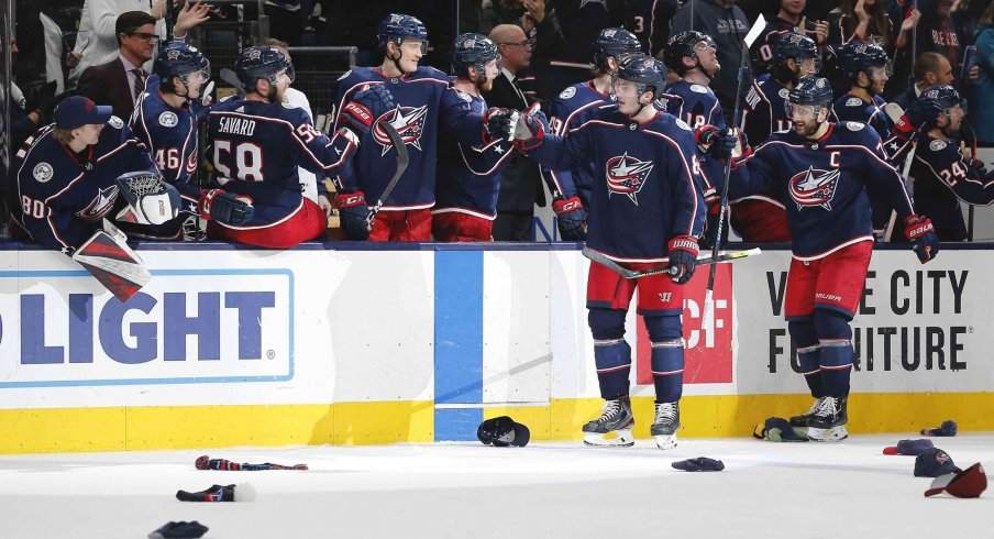 Dec 31, 2019; Columbus, Ohio, USA; Hats begin to hit the ice as Columbus Blue Jackets defenseman Zach Werenski (8) celebrates his first career hat trick during the third period against the Florida Panthers at Nationwide Arena.