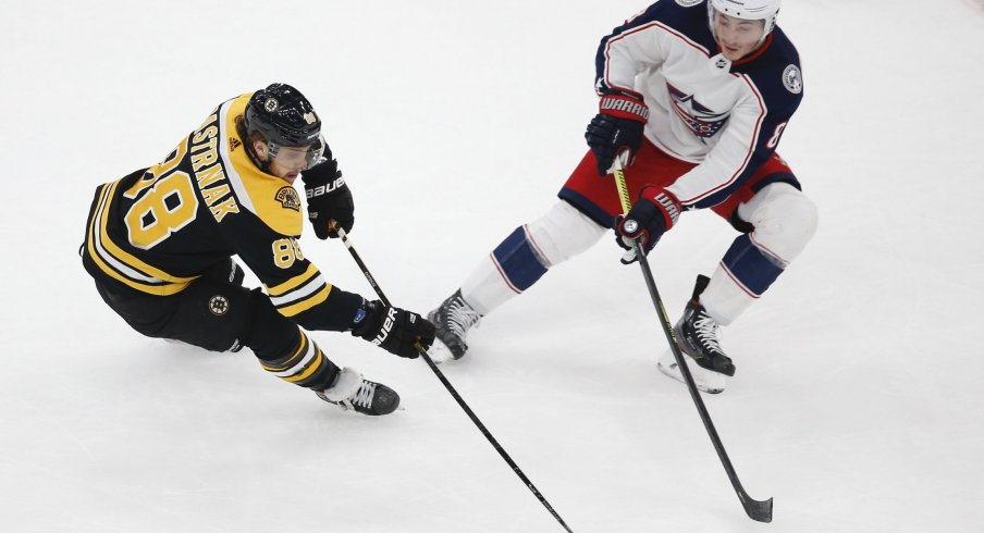 Boston Bruins right wing David Pastrnak (88) keeps the puck away from Columbus Blue Jackets defenseman Zach Werenski (8) during the first period at TD Garden.