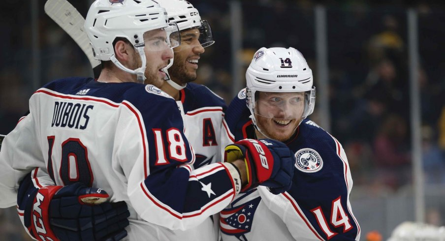 Columbus Blue Jackets center Pierre-Luc Dubois (18) celebrates with defenseman Seth Jones (3) and center Gustav Nyquist (14) after scoring the game winning goal during the overtime period against the Boston Bruins at TD Garden.