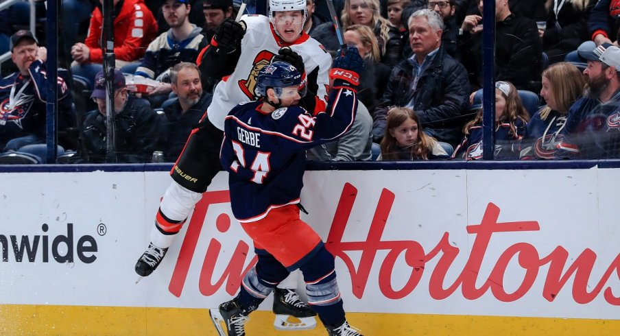 Nathan Gerbe checks Mike Reilly at Nationwide Arena.