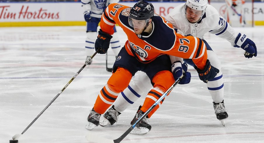 The Edmonton Oilers Connor McDavid and the Toronto Maple Leafs Auston Matthews fight for position
