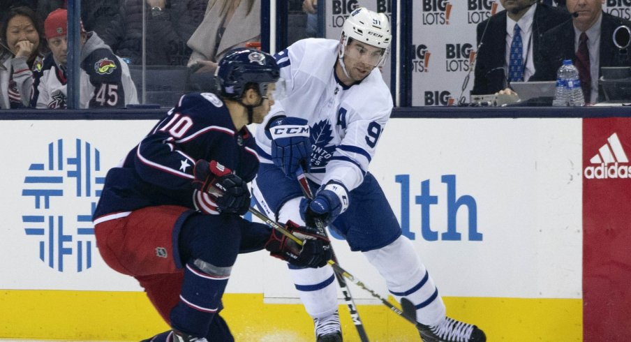 Columbus Blue Jackets center Alexander Wennberg (10) defends against John Tavares of the Toronto Maple Leafs at Nationwide Arena.