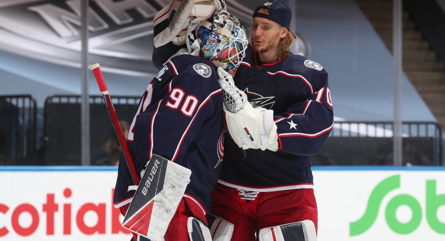 Goaltender Joonas Korpisalo #70 of the Columbus Blue Jackets congratulates fellow netminder Elvis Merzlikins #90 after an exhibition game against the Boston Bruins prior to the 2020 NHL Stanley Cup Playoffs at Scotiabank Arena on July 30, 2020 in Toronto, Ontario. The Blue Jackets defeated the Bruins 4-1.