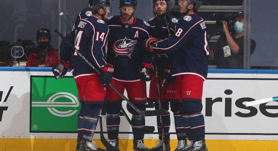 Boone Jenner #38 of the Columbus Blue Jackets celebrates with teammates after Jenner scored during the first period of an exhibition game against the Boston Bruins prior to the 2020 NHL Stanley Cup Playoffs at Scotiabank Arena on July 30, 2020 in Toronto, Ontario.
