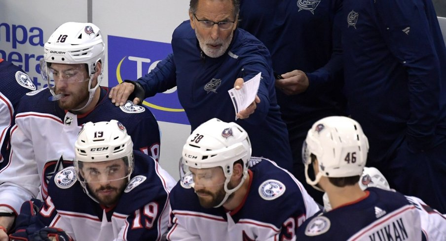 John Tortorella communicates with his players from behind the bench