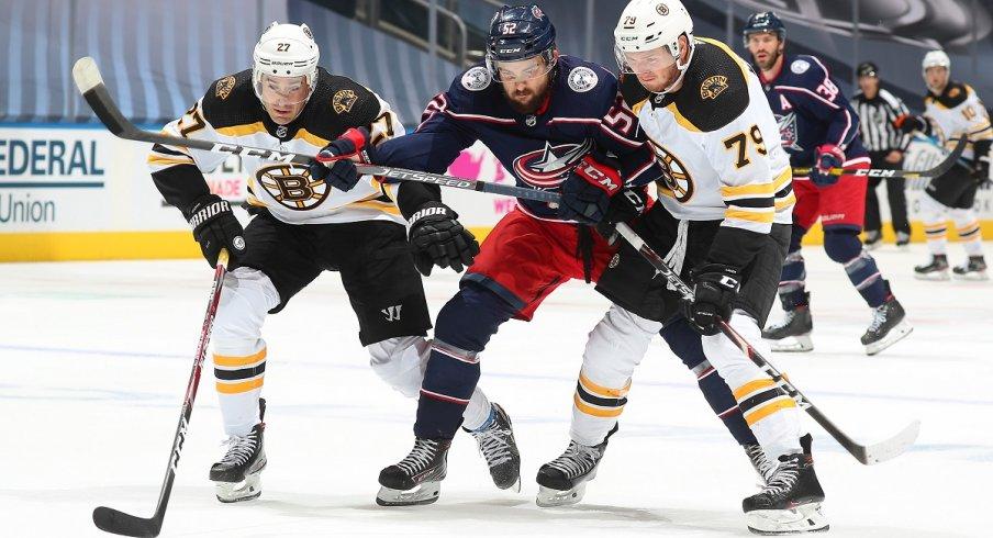 Emil Bemstrom tries to split the Boston Bruins' defense