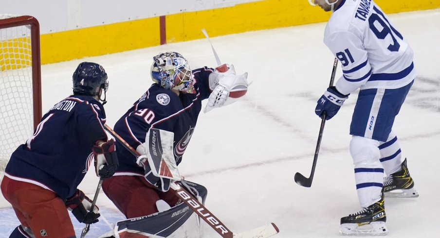 Elvis Merzlikins makes a glove save as Toronto Maple Leafs forward John Tavares