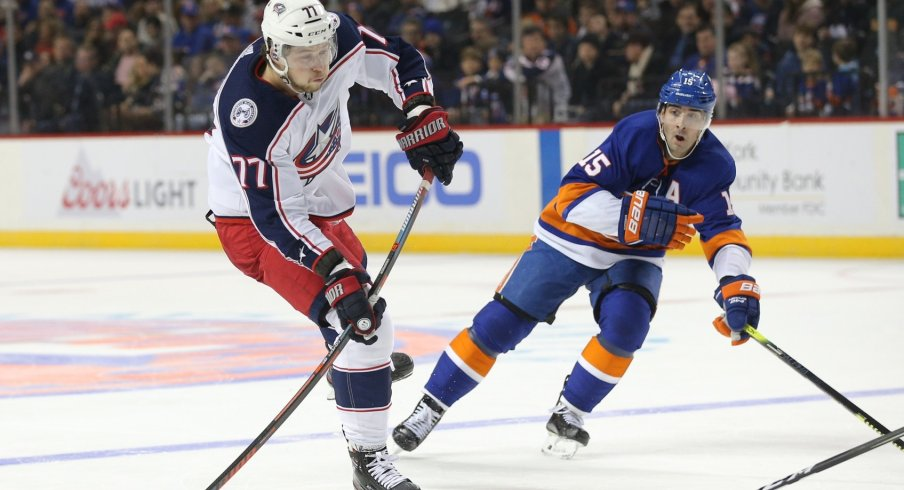 Former Columbus Blue Jacket Josh Anderson tries to get rid of the puck before he is tracked down by Islanders forward Cal Clutterbuck.