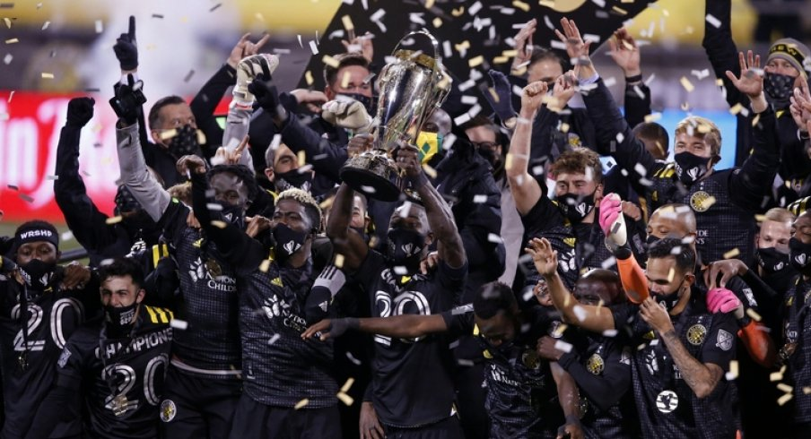 Columbus Crew defender Jonathan Mensah (4) hoists the MLS Cup trophy with his teammates after their 3-0 win over the Seattle Sounders in the MLS Cup at MAPFRE Stadium.