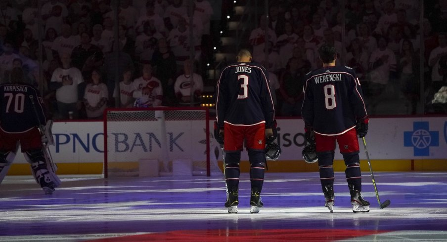 Zach Werenski and Seth Jones during the National Anthem before a game against the Carolina Hurricanes at PNC Arena