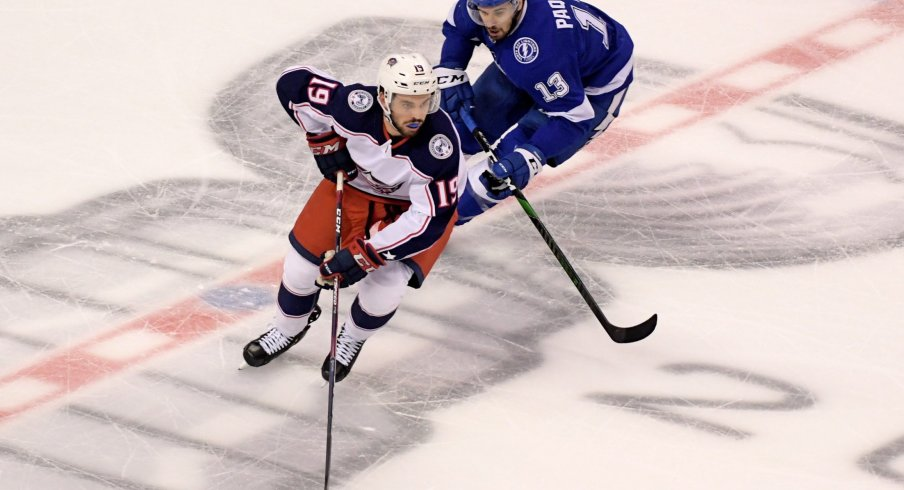 Aug 13, 2020; Toronto, Ontario, CAN; Columbus Blue Jackets center Liam Foudy (19) skates with the puck away from Tampa Bay Lightning center Cedric Paquette (13) during the first period in game two of the first round of the 2020 Stanley Cup Playoffs at Scotiabank Arena.