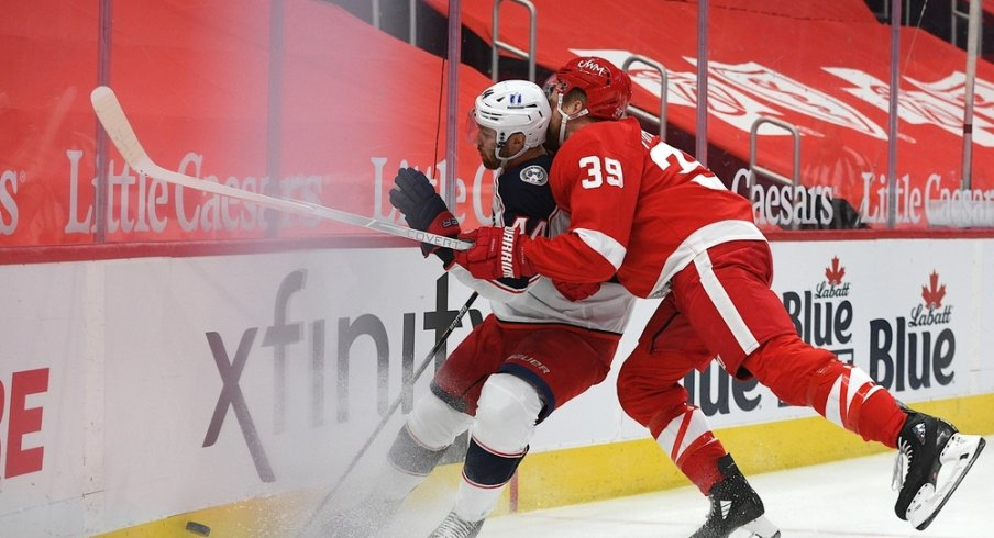 Detroit Red Wings right wing Anthony Mantha (39) checks Columbus Blue Jackets defenseman Vladislav Gavrikov (44) during the second period at Little Caesars Arena.