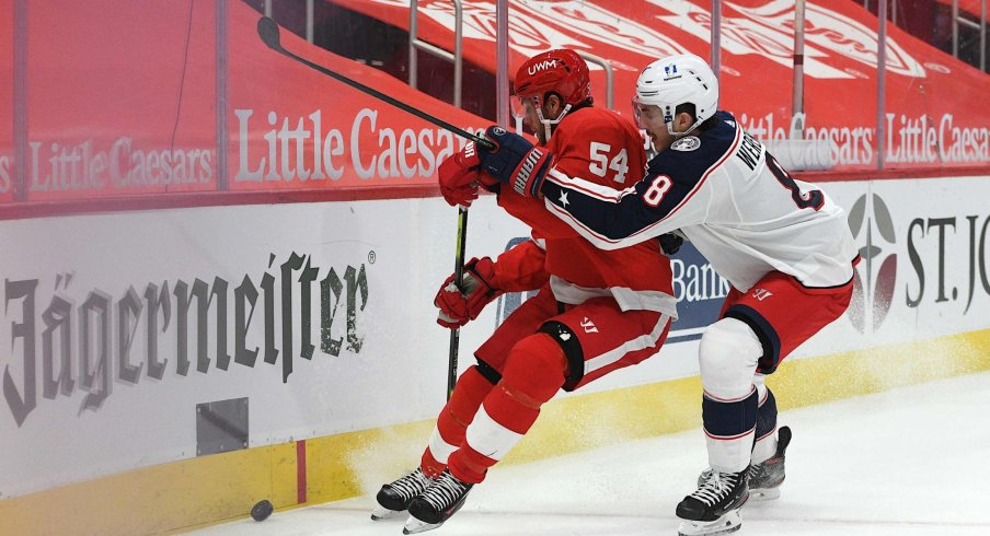 Jan 18, 2021; Detroit, Michigan, USA; Columbus Blue Jackets defenseman Zach Werenski (8) checks Detroit Red Wings right wing Bobby Ryan (54) during the second period at Little Caesars Arena.