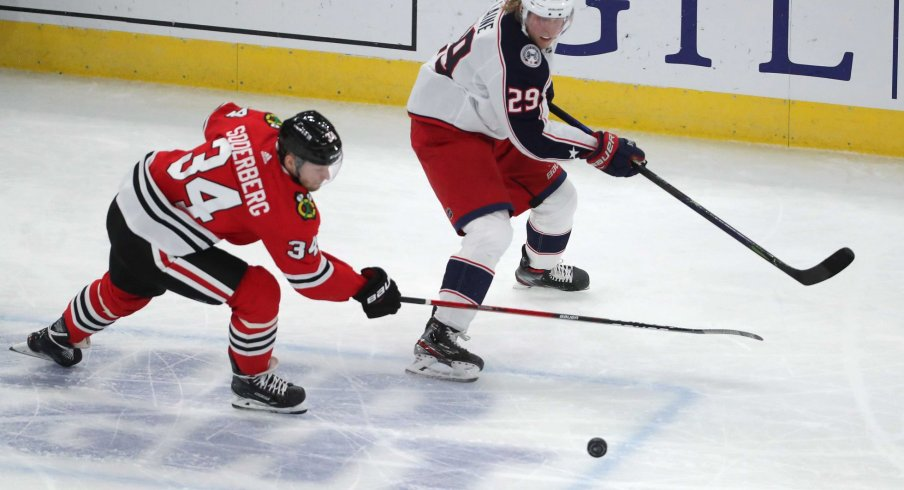 Feb 13, 2021; Chicago, Illinois, USA; Chicago Blackhawks center Carl Soderberg (34) and Columbus Blue Jackets right wing Patrik Laine (29) chase the puck during the third period at the United Center. Chicago won 3-2 in overtime.