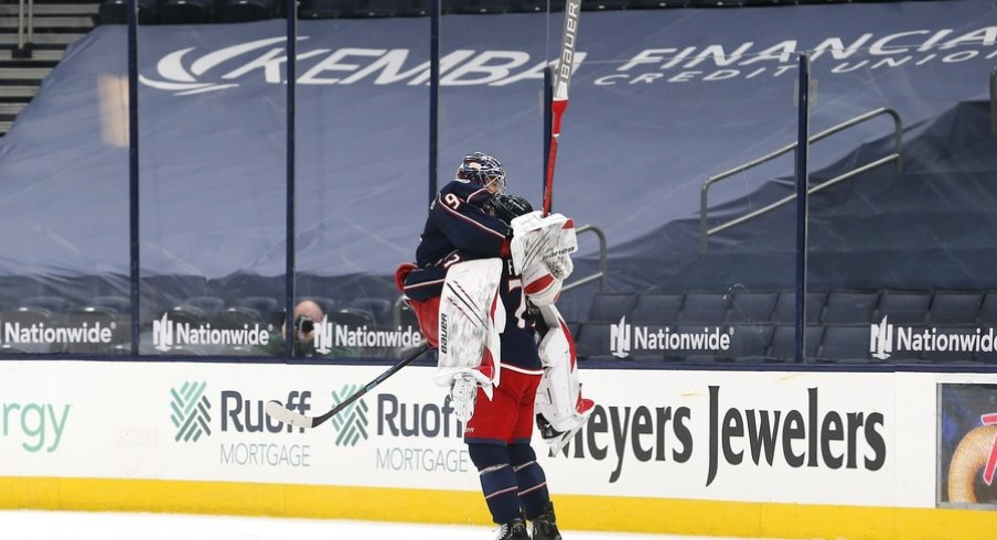 Columbus Blue Jackets goalie Elvis Merzlikins (90) and left wing Nick Foligno (71) celebrate the win after the game against the Nashville Predators at Nationwide Arena.