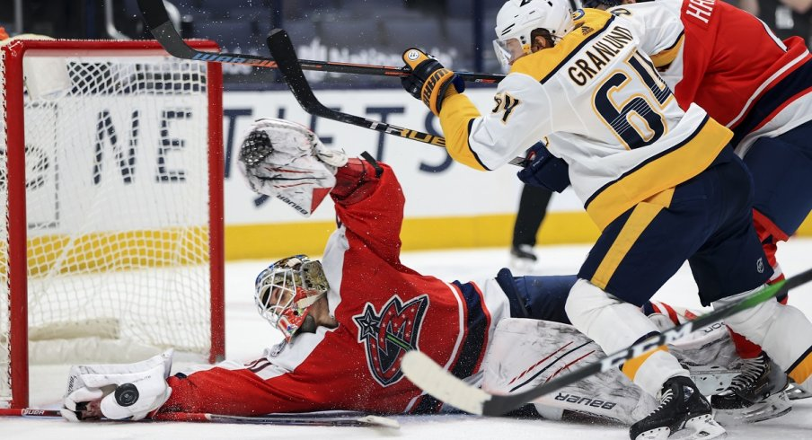 Elvis Merzlikins reaches to make a save against Nashville Predators center Mikael Granlund
