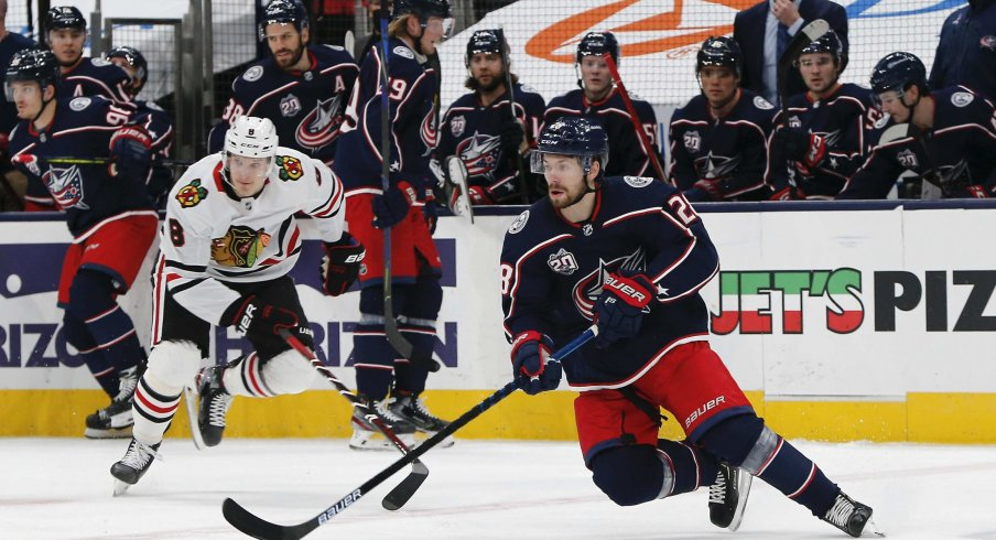Feb 25, 2021; Columbus, Ohio, USA; Columbus Blue Jackets right wing Oliver Bjorkstrand (28) grabs a loose puck against the Chicago Blackhawks during the first period at Nationwide Arena.