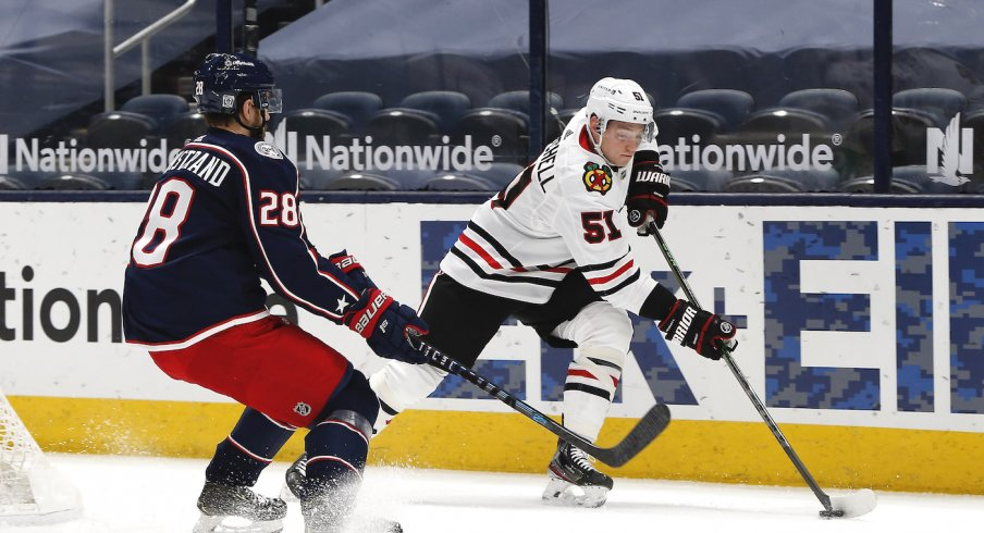 Chicago Blackhawks defenseman Ian Mitchell (51) and Columbus Blue Jackets right wing Oliver Bjorkstrand (28) chase down a loose puck during the first period at Nationwide Arena.