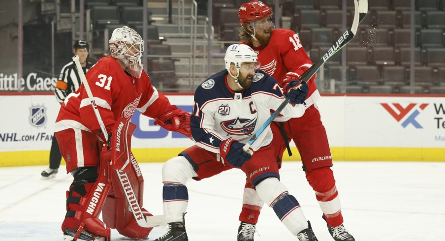 Columbus Blue Jackets left wing Nick Foligno (71) and Detroit Red Wings defenseman Marc Staal (18) fight for position with in front of goaltender Calvin Pickard (31) in the first period at Little Caesars Arena.