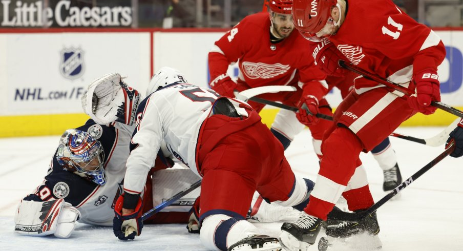 Detroit Red Wings right wing Filip Zadina (11) and Columbus Blue Jackets defenseman David Savard (58) battle for the puck in front of. goaltender Elvis Merzlikins (90) in the second period at Little Caesars Arena.