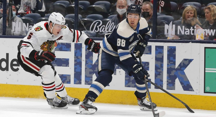 Apr 12, 2021; Columbus, Ohio, USA; Columbus Blue Jackets right wing Kole Sherwood (88) picks up a loose puck as Chicago Blackhawks defenseman Connor Murphy (5) defends during the first period at Nationwide Arena.