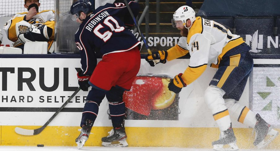 May 5, 2021; Columbus, Ohio, USA; Columbus Blue Jackets left wing Eric Robinson (50) and Nashville Predators defenseman Mattias Ekholm (14) battle for the puck during the first period at Nationwide Arena.